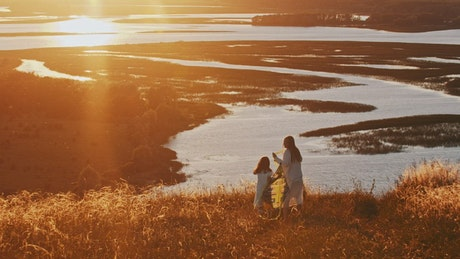 Woman and her daughter walking with a kite at the sunset