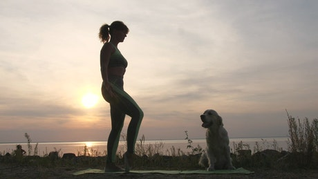 Woman and her dog doing yoga in front of the sea