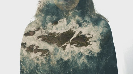 Woman and sea waves hitting a cliff