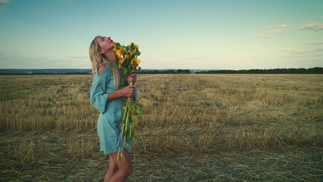 Woman and sunflowers in the dry field, fashion concept