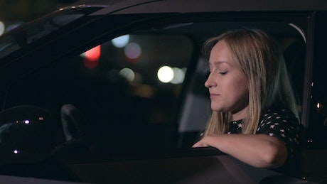 Woman answering a call in her car at night