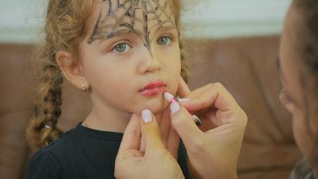 Woman applies lipstick to little girl for Halloween