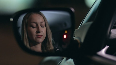 Woman applying lipstick in a car