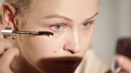 Woman applying makeup to her eyes