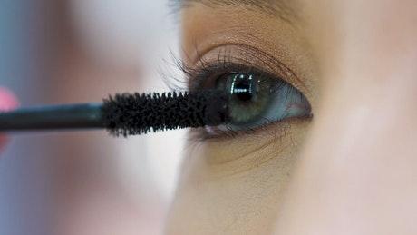Woman applying mascara in her eyes