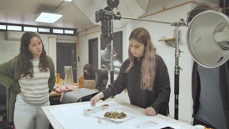 Woman arranges food composition for photo
