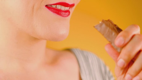 Woman biting a chocolate on a yellow background