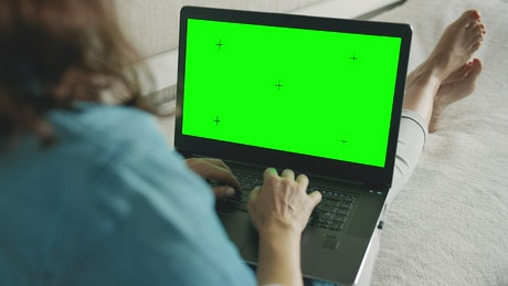 Woman browsing website on laptop greenscreen in bed