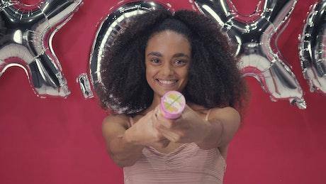 Woman bursting a confetti cannon