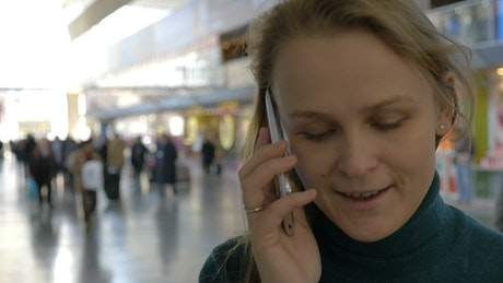 Woman calling a friend from a train station
