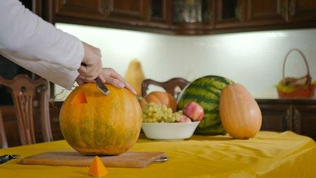 Woman carves pumpkin into Jack-O-Lantern on kitchen table