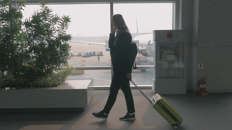 Woman chatting on the phone at an airport