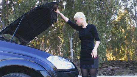 Woman checking the oil level in her car