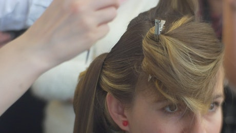 Woman combing blonde hair of a girl