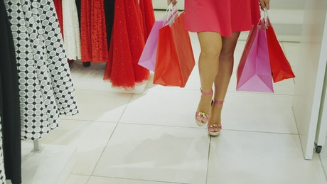 Woman comes out of a store with shopping bags