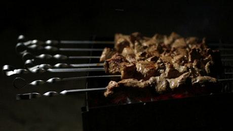 Woman cooking meat skewers