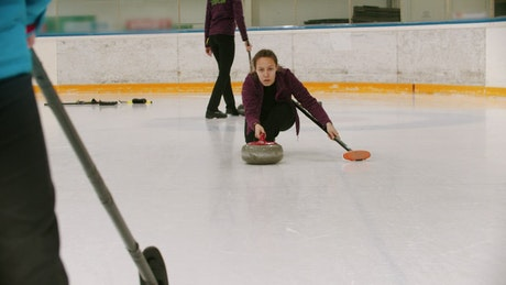 Woman curling player sliding on ice