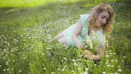 Woman cutting flowers lying down in nature