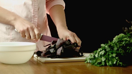 Woman cutting herbs in the kitchen table
