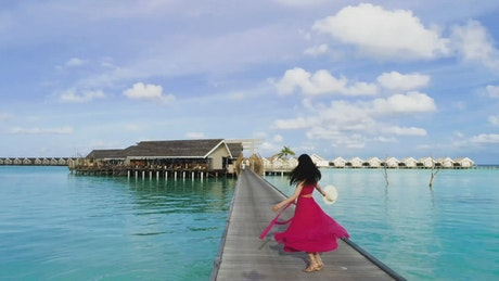 Woman dances in front of an ocean villa