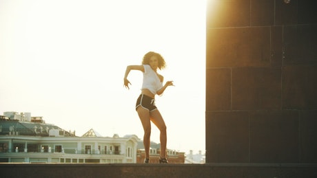 Woman dancing captivatingly on top of a building