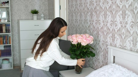 Woman decorates her room with flowers