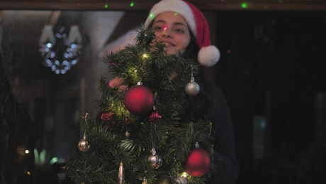 Woman decorating a small Christmas tree