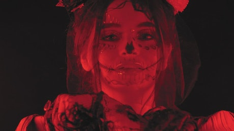 Woman disguised as a catrina under a dim red light