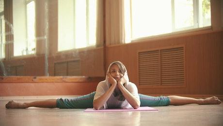 Woman doing a split on the floor of a dance gym