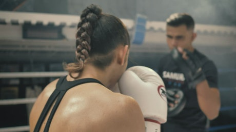 Woman doing kickbox movements with a coach