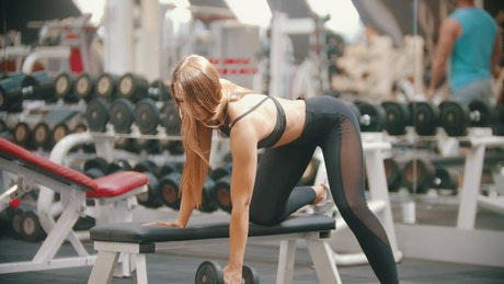 Woman doing repetitions with a dumbbell in a gym