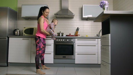 Woman doing squats with her baby in arms