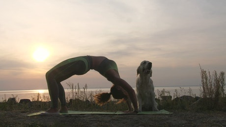 Woman doing Yoga at the beach