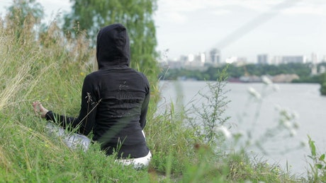 Woman doing Yoga by a city river
