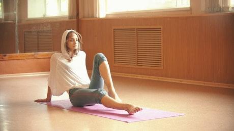 Woman doing yoga on a mat on the floor