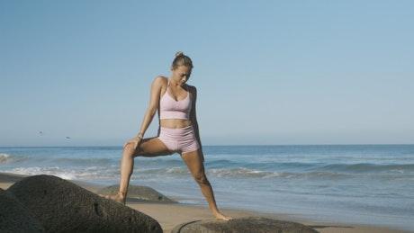 Woman doing yoga on boulders on the beach