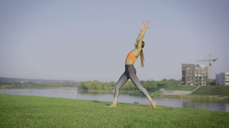 Woman doing yoga on the grass