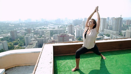 Woman doing yoga pose on rooftop with city panorama
