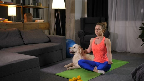 Woman doing Yoga with her pet dog