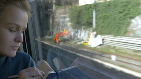 Woman drawing during a train journey