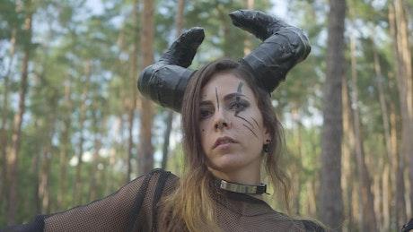 Woman dressed as devil dances in woods