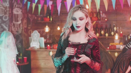 Woman drinking at a Halloween party