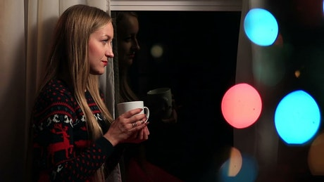 Woman drinking coffee by festive lights