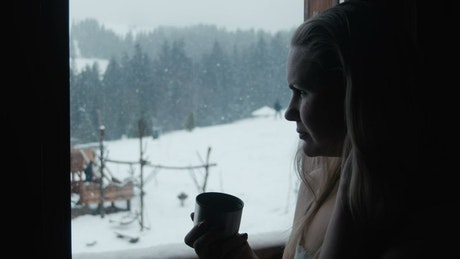 Woman drinking coffee by the window on a snowy day