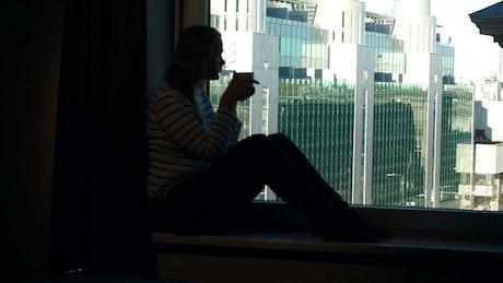 Woman drinking coffee in a dark room
