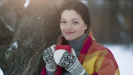 Woman drinking coffee in winter park