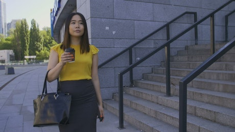 Woman drinking coffee while walking to work