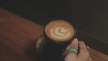 Woman drinking from a cup of frothy coffee