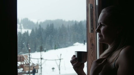 Woman drinking tea by the window on a snowy day