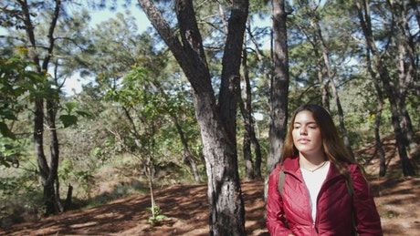 Woman drinking water in the forest